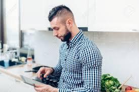tablette pour cuisine enthousiaste homme dans la cuisine nouvelle cuisine en utilisant la