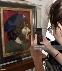 A Woman Takes A Picture Of A Painting Of Argentine Born Guerrilla