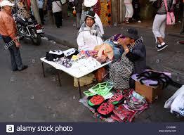 aymara ladies selling masks for halloween in street market la paz