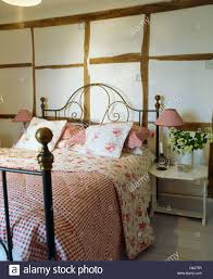 pink checked and rose patterned quilt on wrought iron bed in
