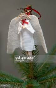 homemade clothes peg angel decoration on top of christmas tree