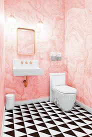 pink bathroom with black and white tile and marble wallpaper and