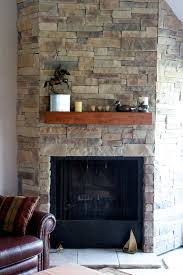 ledge stone fireplace installed over drywall with a spruce beam