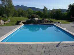 wondrous stones pavers around rectangular pool and stone waterfall