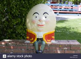 a statue of humpty dumpty sat on a brick wall stock photo