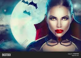 halloween vampire woman portrait over scary night background