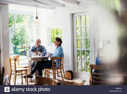 two people seated at a coffee shop table by a window blurred