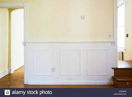 a wall with traditional paneled wainscoting and door molding in an