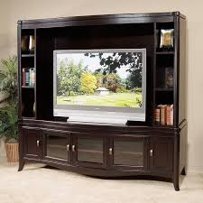 dark wooden entertainment center with glass doors and narrow