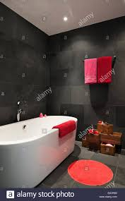 bright red and pink towels in bathroom with slate tiling and