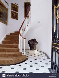black and white tiled floor and brown carpet on curved staircase