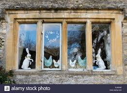 easter rabbits and chicken ornaments standing in a cottage window