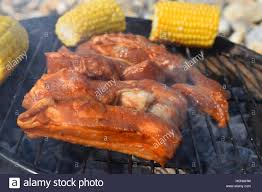Outdoor Barbecue Close Up Of Marinated Ribs With Sweet Corn On An Outdoor Barbecue