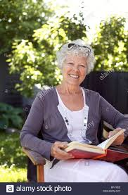 Chair In Garden Elderly Woman Relaxing On A Chair In Garden With A Book Looking At