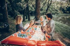 young family playing with son on a hammock in park on camping