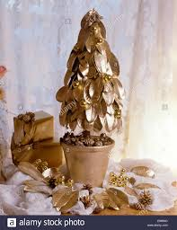 close up miniature christmas tree made from gold painted leaves