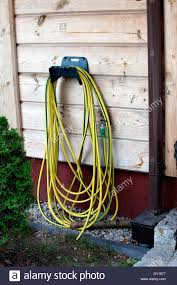 yellow and green striped garden hose hung on a hook spala central