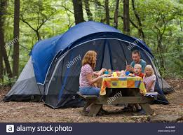 Camping Picnic Table Camping Family Eating Dinner At Picnic Table With Tent In The