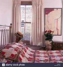 patchwork quilt on brass bed in cottage bedroom with white