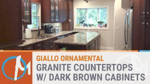 giallo ornamental granite countertops with brown cabinets