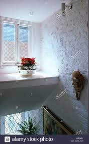 White Marble Window Sills Red Geranium In Pot On Landing Window Sill With Brick Wall Painted