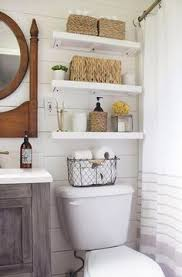 floating shelves above the toilet in this bathroom is much