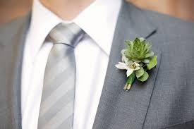 succulent boutonniere groom wears grey tailored suit and succulent boutonniere