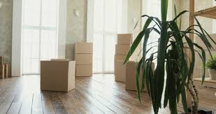 Moving To A New Property by New Home Owners Unpacking Boxes Big Cardboard Boxes In New Home