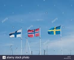 Scandanavian Flags Three Scandinavian Flags In A Marina On A Blue Summer Sky Stock