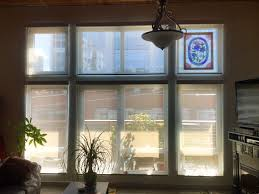 a wall of outside mount motorized solar shades with aluminum