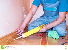 Laminate Flooring With Free Installation Repairman Installing Skirting Board Oak Wooden Floor With Caulking