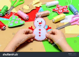 small child holding felt christmas snowman stock photo 517234351