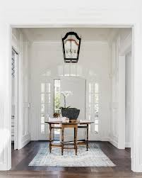 White Foyer Table A White Front Door Framed With Arch Windows And Sidelights Open To
