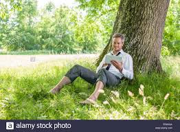 looking with grey hair a nice looking grey hair man is sitting against a tree in the