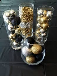 gold black and silver ornaments in glass cylinders