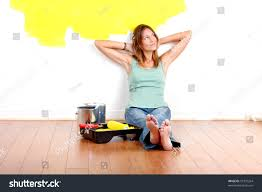 smiling beautiful woman painting interior wall stock photo