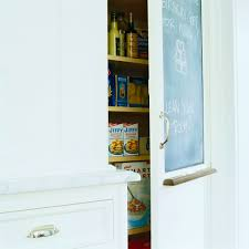 a chalkboard replaces one of the door panels on a kitchen cabinet