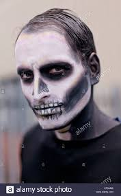 Skeleton Face Painting For Halloween by Man Made Up With Face Paint To Look Like A Scary Skeleton Stock