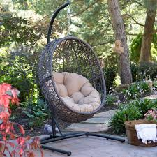 round dark brown rattan hanging swing chair with shabby grey
