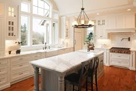 white kitchen with island christmas lights decoration large ceiling height window affords natural light in this white kitchen centered around large marble topped