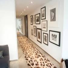 small hallway design with runner rugs and framed wall gallery