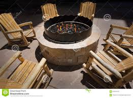 Wooden Rocking Chairs by Large Outdoor Fire Pit Surrounded By Wooden Rocking Chairs Stock