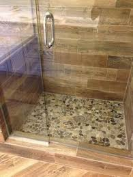 cool wood grain porcelain shower and river rocks stephen belyea