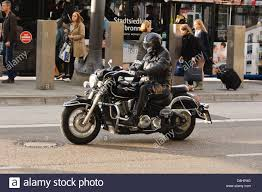 cheap motorbike clothing biker in black motorcycle clothing and black helmet riding a