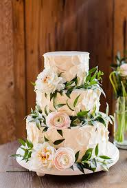 wedding cake greenery brides three tiered white wedding cake covered in flowers and