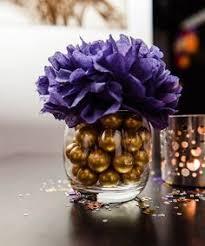 purple flower arrangement atop a glass vase with gold ornaments