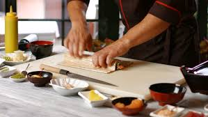 japanese restaurant cook at table stock video of man s hands making sushi rolls man in robe cooking