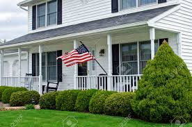 white two story colonial house with american flag stock photo