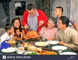 thanksgiving celebrate latin family watches grandfather carve turkey thanksgiving meal