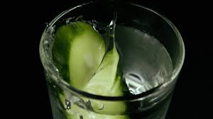 green cocktail black background oval cut of cucumber drops into icy water in a glass on a black